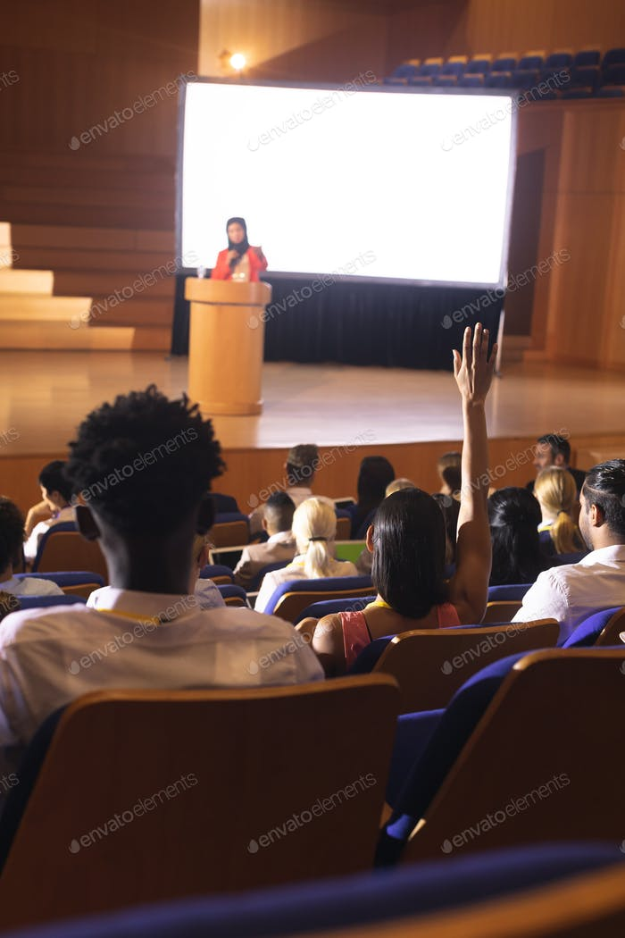 Front view of mixed race woman sitting in audience raising hand for asking question