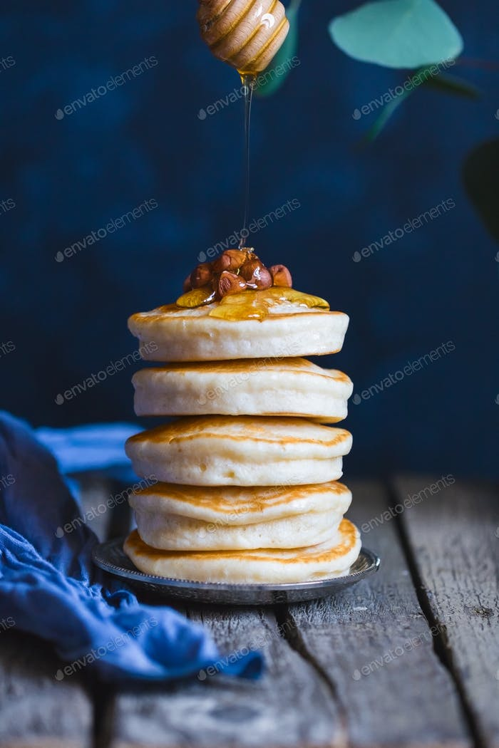 Stack of pancakes with honey and nuts.