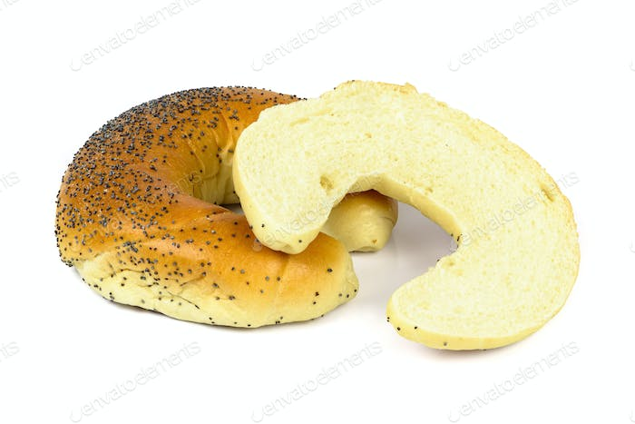Cut crescent roll with poppy seeds on white background