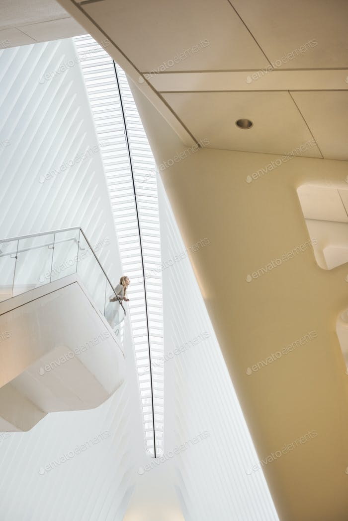One person standing on a floating suspended balcony in the open space of a white atrium