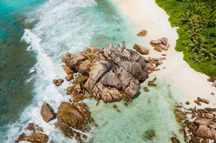 Seychelles La Digue Island. Aerial view of ocean waves and huge granite rocks on the tropical beach