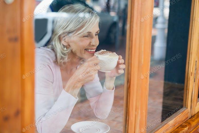 Lächelnde Senior Frau trinken Kaffee während sitzen am Tisch