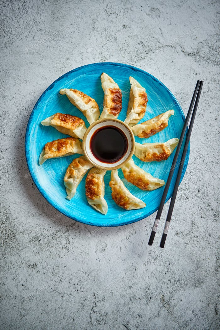 Traditional asian dumplings Gyozas on turqoise ceramic plate