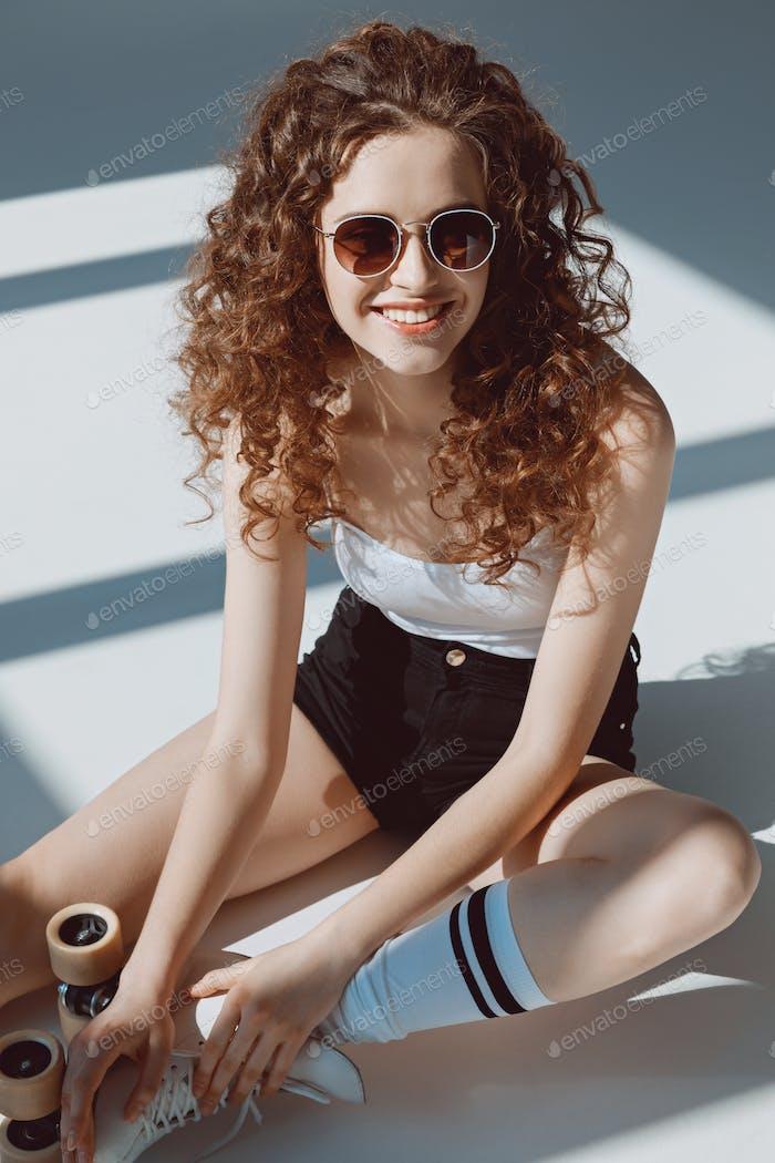 schöne rote Haare Hipster Mädchen in Sonnenbrille sitzen auf dem Boden, Hipster Mädchen lächelnd