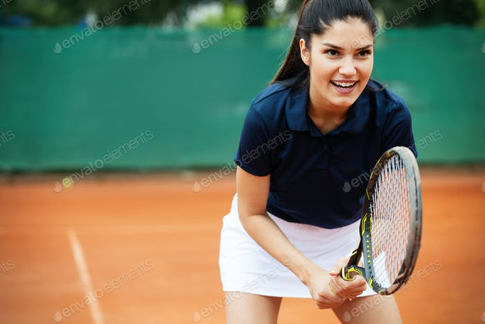 Portrait of forceful woman playing tennis on outdoor tennis court