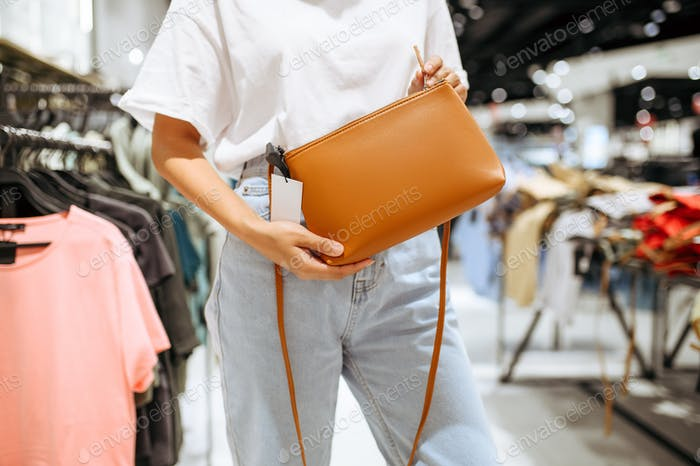 Woman holds handbag in clothing store