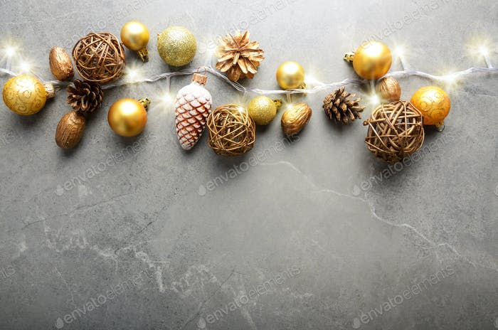 Flat lay view at Christmas decorations of gold and yellow cones glass balls and light garland