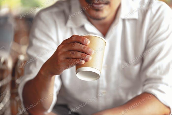 Nahaufnahme des jungen Mannes, der Kaffee hält, um am frühen Morgen zu Hause wegzunehmen, verschwommener Hintergrund