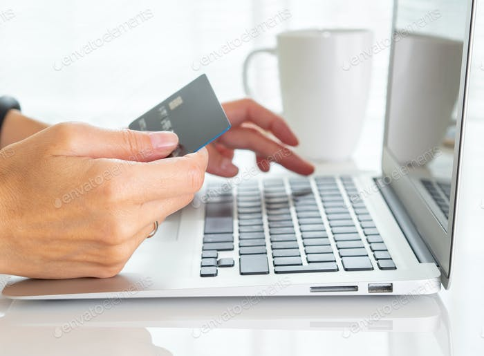 woman sitting at table, drinking tea and looking at laptop, pay for purchases by credit card