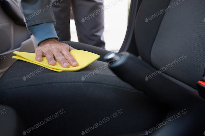 Worker cleaning seat inside the car