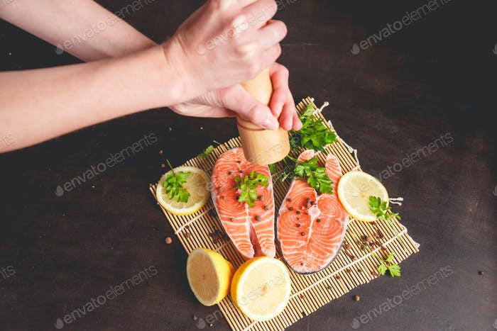 A woman sprinkles salmon with pepper from a pepper mill