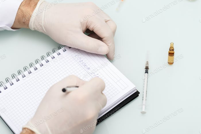 Doctor wearing gloves and writing Corona Virus