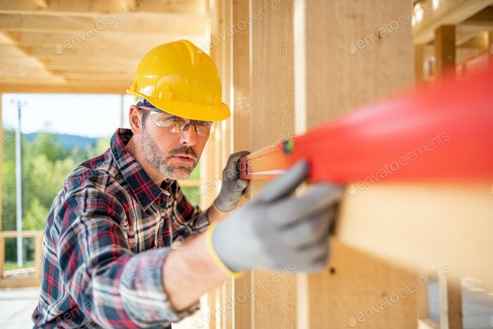 Worker using level tool measure frame house construction
