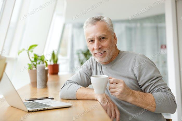 Senior businessman sit in cafe drinking coffee.