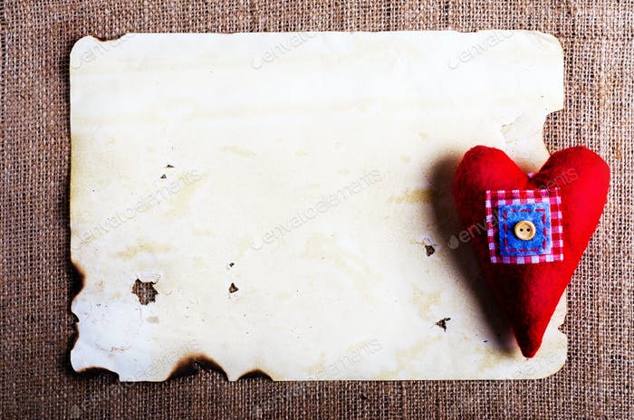 Old vintage sheet of paper and red textile heart on burlap, sackcloth background. Retro design