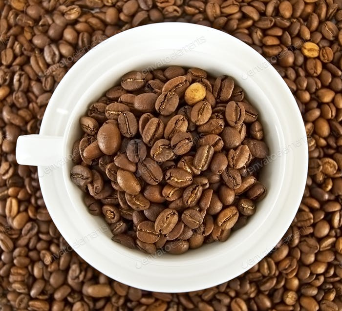 Coffee beans in the cup against the grain of