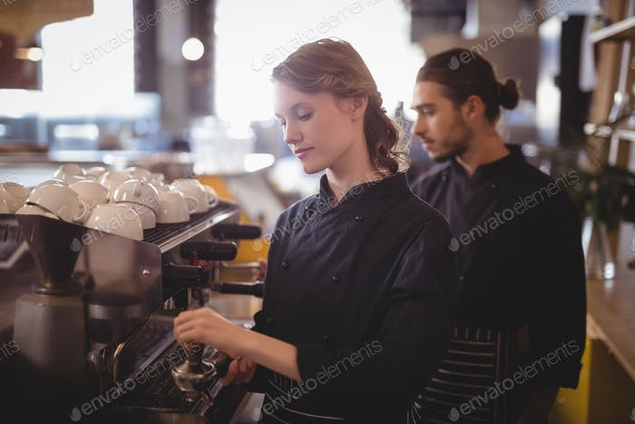 Young wait staff using espresso maker at coffee shop
