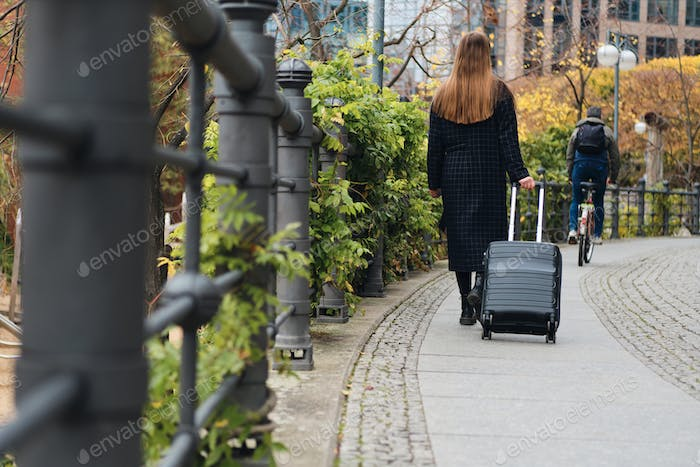 Back view of casual girl in coat walking through street with suitcase