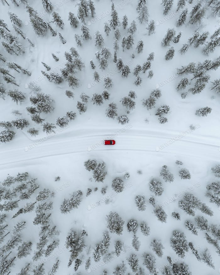 Drone view of a red car driving though a snowy forest in Lapland, Finland