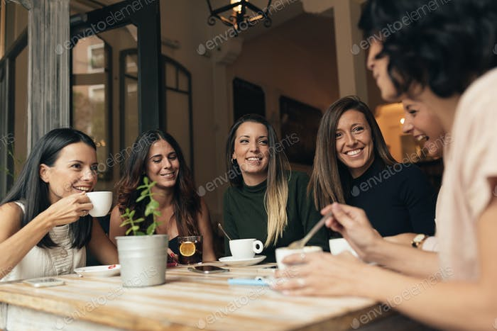Seis hermosas mujeres bebiendo café y charlando.