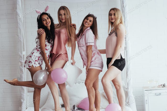 Four beautiful girls in night wear have party
