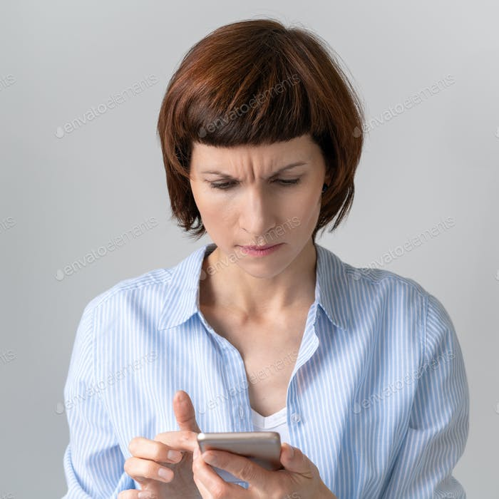 Middle-aged woman looking at phone and frowning. Wrinkle on forehead