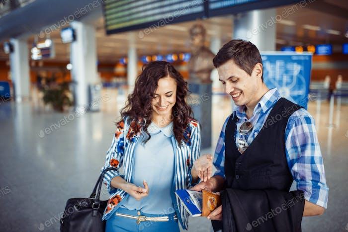 Junges liebevolles Paar umarmt im Flughafenterminal.