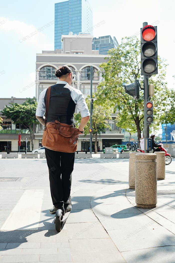 Entrepreneur riding scooter in city