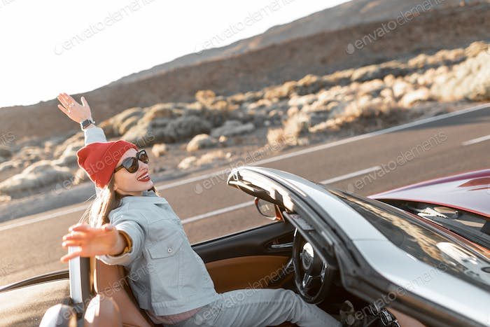 Happy woman traveling by cabriolet car