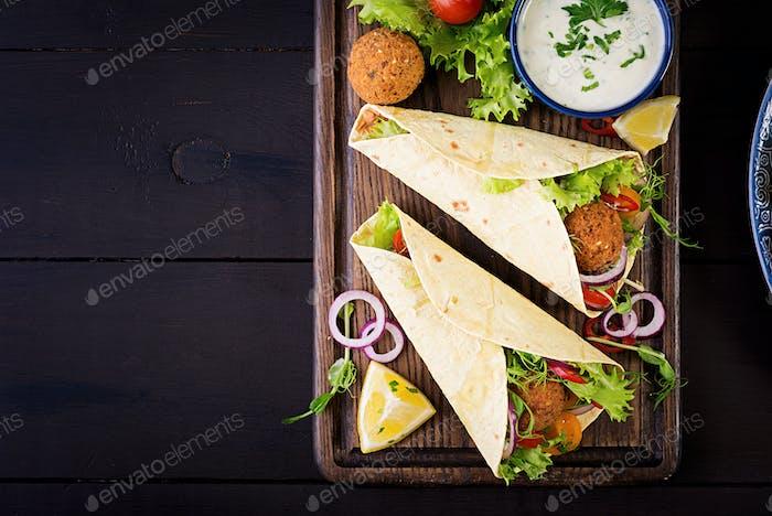 Tortilla wrap with falafel and fresh salad. Vegan tacos. Vegetarian healthy food. Top view