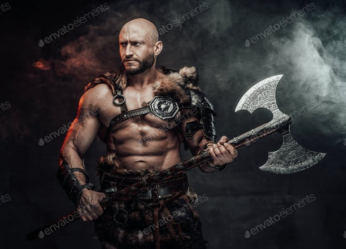 Handsome viking in antique clothing with axe in smokey background