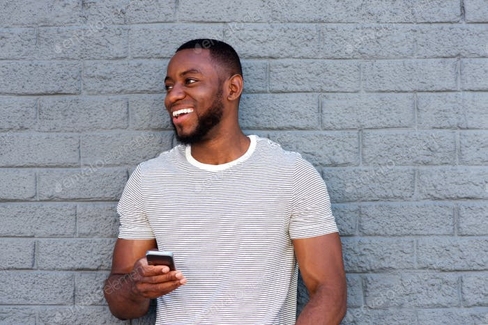 smiling man with cell phone leaning on gray wall