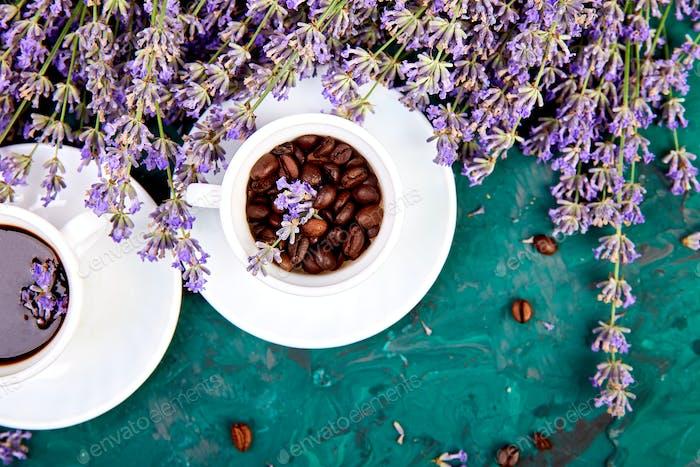 Kaffee, Kaffeekorn in Tassen und Lavendelblüte auf grünem Hintergrund