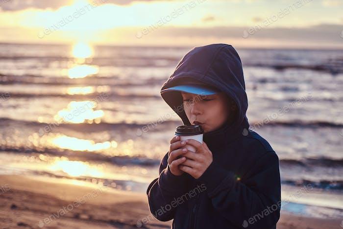 Little boy is drinking tea at seaside, on sunset time