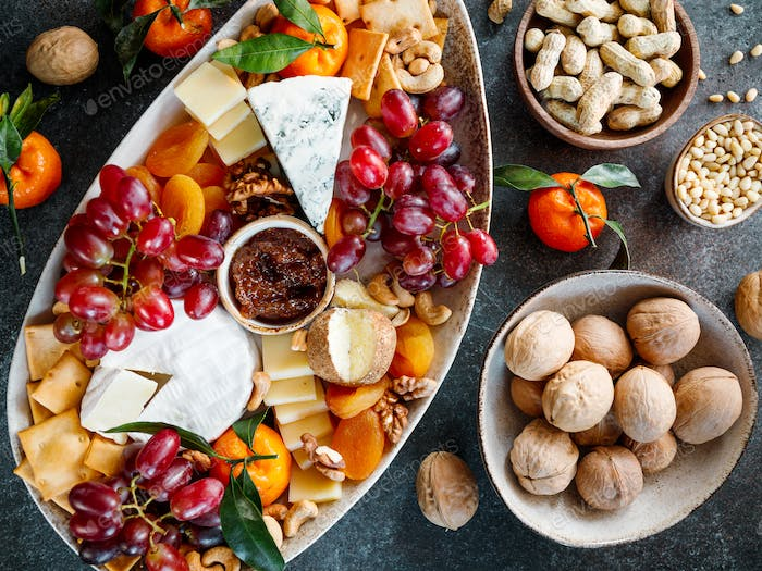 Big cheese board with appetizer assortment. Grape, cheese, nuts, jam and bread.
