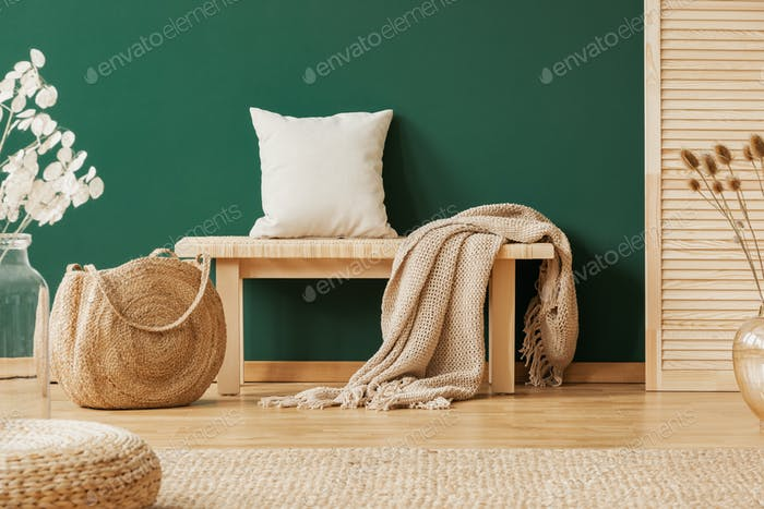 Wooden bench with beige carpet and pillow next to straw handbag, copy space on the empty green wall