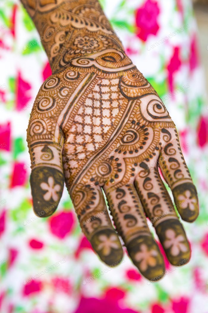 Female hand covered in Henna tattoos