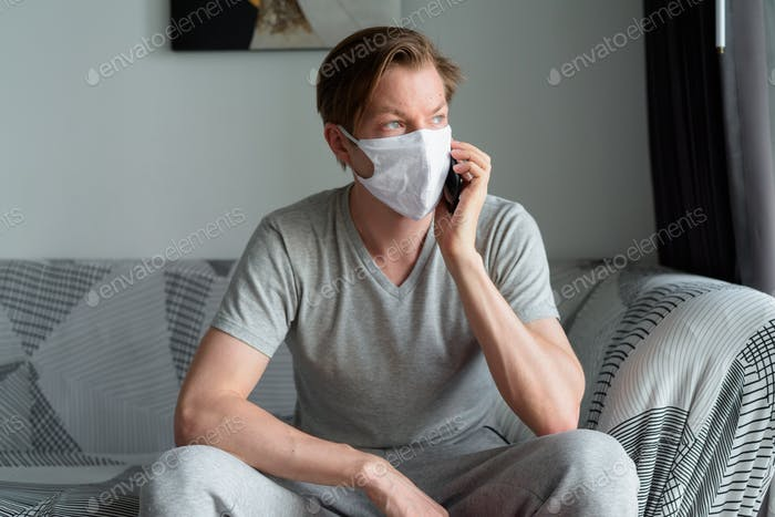 Young man with mask talking on the phone at home under quarantine