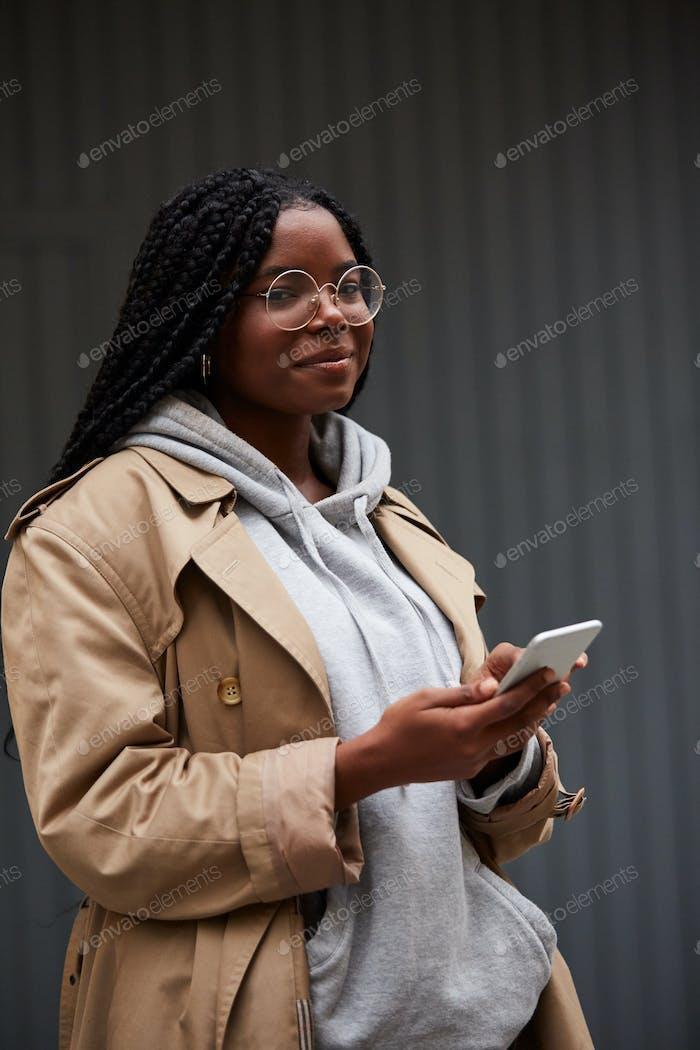 Black woman using smartphone on street