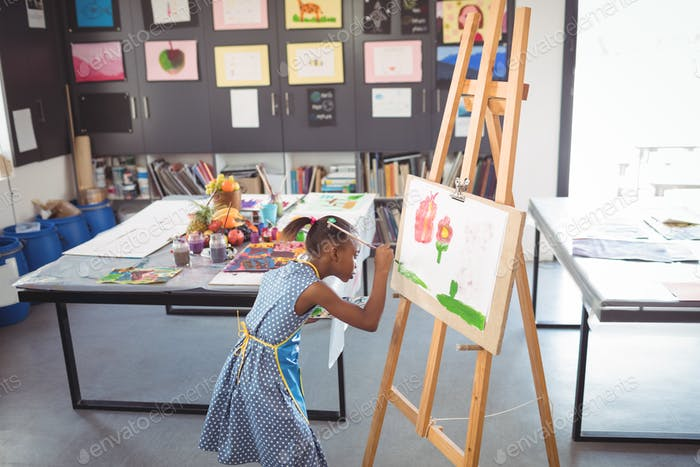 High angle view of focused girl painting on canvas