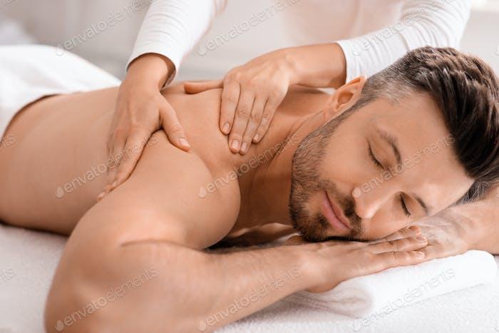 Крупным планом красивый мужчина, имеющий массаж всего тела в спа