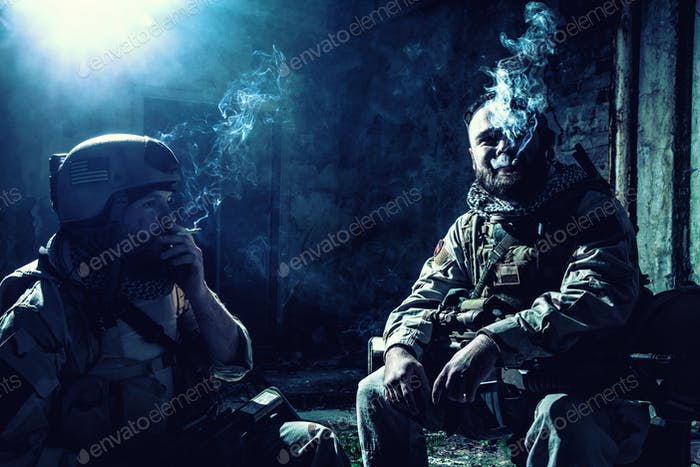Tired commando soldiers smoking after intensive firefight