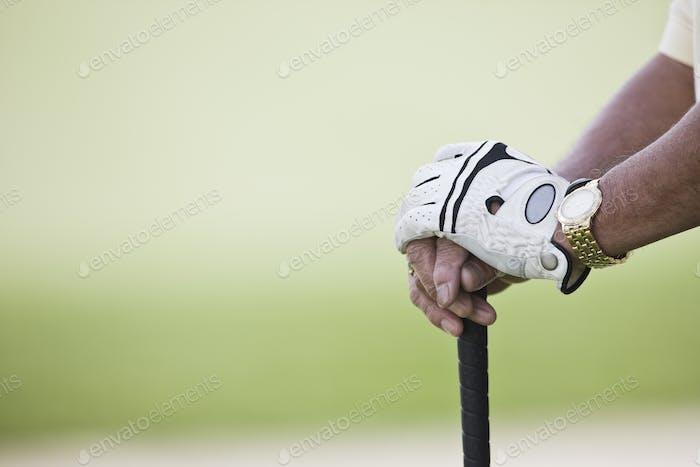 Крупным планом рук и гольф-клуб.