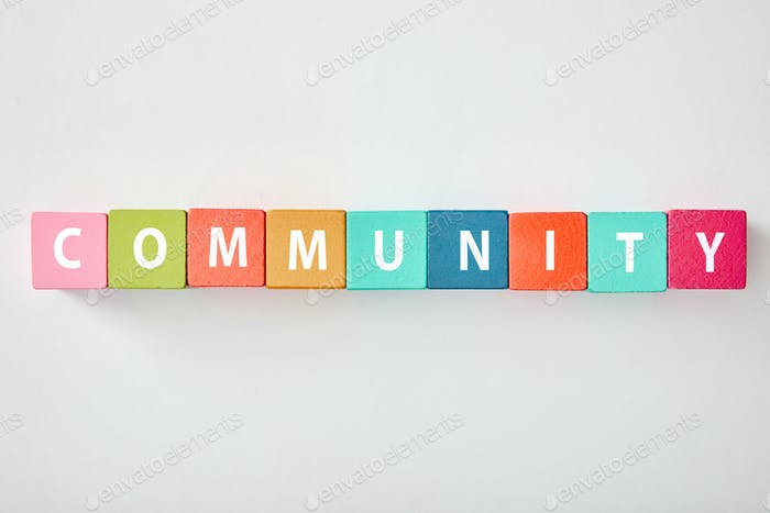 vista superior de letras Comunidad hechas de cubos multicolores sobre fondo gris
