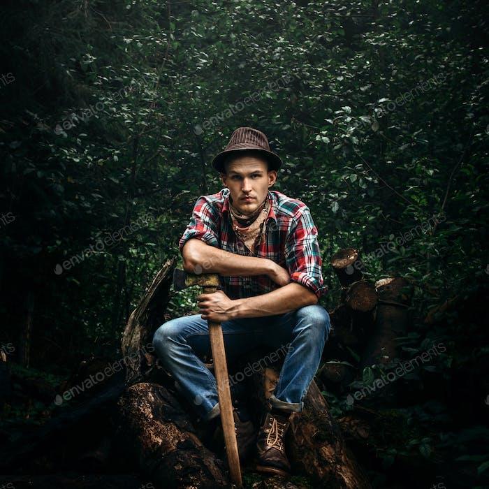 стильный хипстерский лесоруб с топором в солнечном лесу в горах