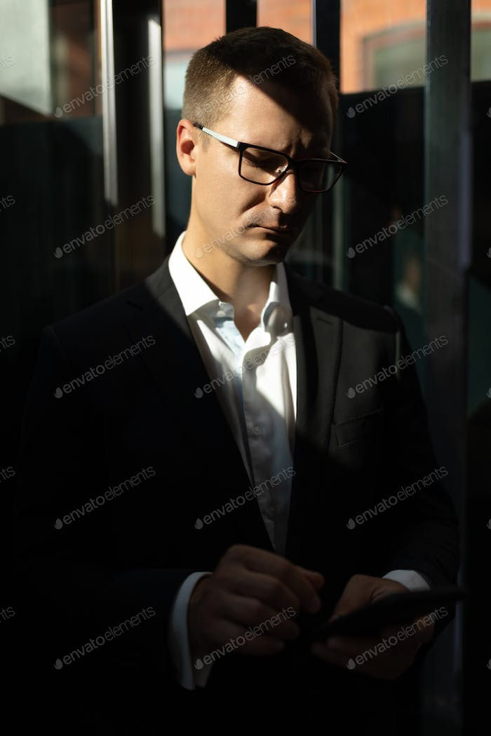 Businessman with smartphone in elevator