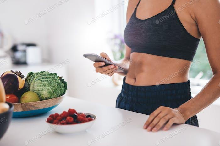 Junge Frau mit Handy in der Küche