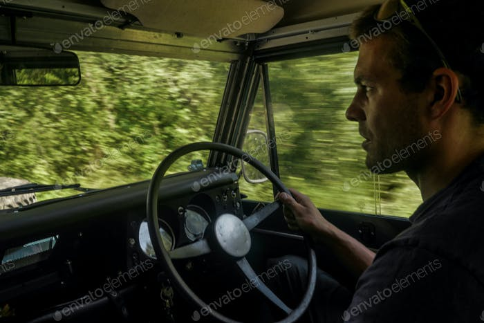 caucasian man driving a off road jeep
