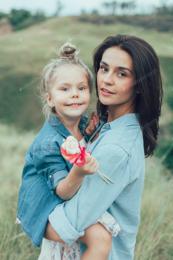 The young mother and daughter on green grass background photo by