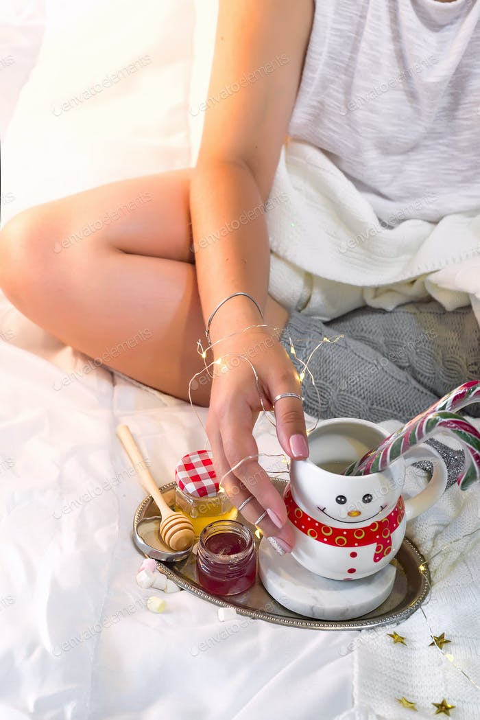 Female hands hold a cup in the form of a snowman with Christmas candies, honey and jam on the bed